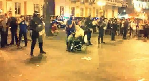 Un hombre en silla de ruedas hace un slalom entre los antidisturbios de la Puerta del Sol