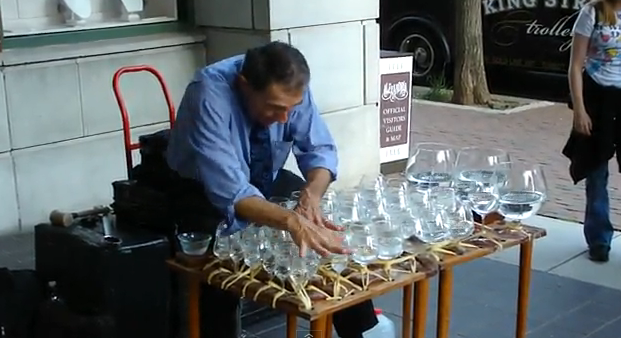 Músico callejero tocando Mozart en vasos de agua