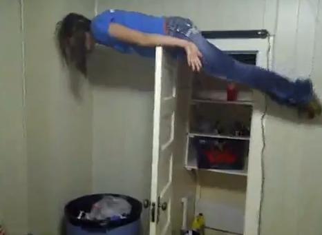 Chica haciendo planking sobre una puerta