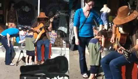 Un niño ciego y autista disfruta de la música de un artista callejero