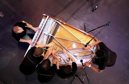 Cinco hombres tocando el piano
