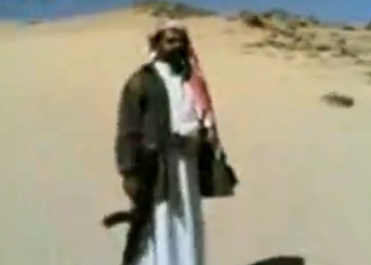 Un hombre enciende un cigarrillo con un AK-47