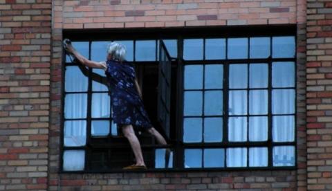 Una abuela limpiando la ventana de su casa a fondo