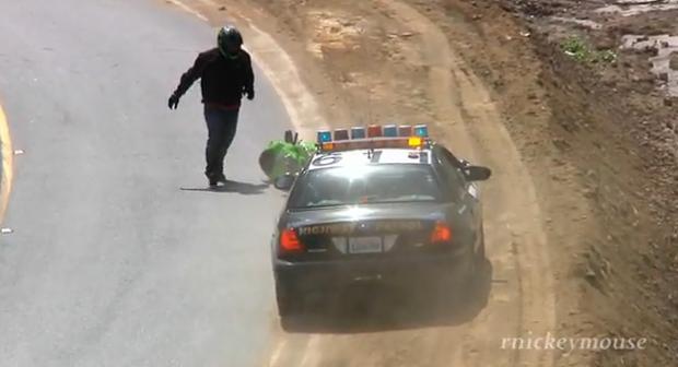 Frena al ver la patrulla de policía y se cae de la moto