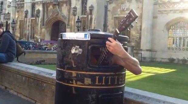 Un músico callejero canta y toca la guitarra dentro de una papelera