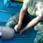 Un soldado sirio a bordo de un helicóptero enciende la mecha de una bomba casera y la lanza a un pueblo