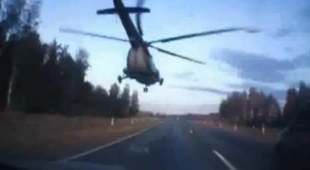 Un helicóptero militar Mi-8 adelanta a una gran cantidad de coches en una autovía rusa