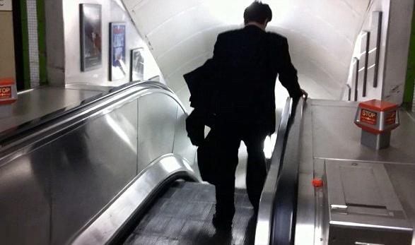 Borracho intentando bajar las escaleras mecánicas por el lado contrario