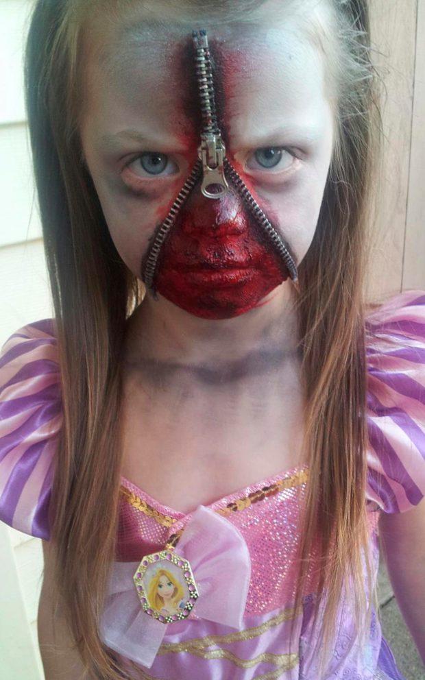 Niña disfrazada de princesa sangrienta con una cremallera en la cara