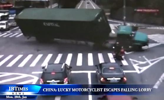 Un motorista afortunado escapa de ser aplastado por un camión