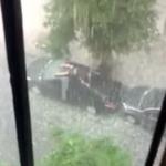 Un hombre intenta proteger su coche de una tormenta de granizo