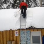 Mientras uno quita la nieve del tejado, los demás miran como casi se parte la crisma