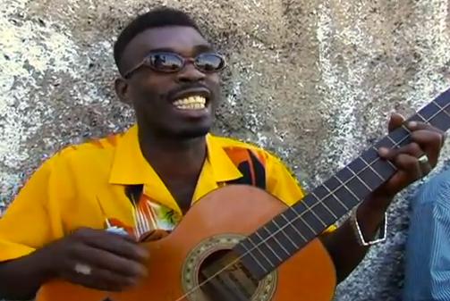 Brushy One String cantando 'Chicken In The Corn' acompañado de una guitarra de una sola cuerda