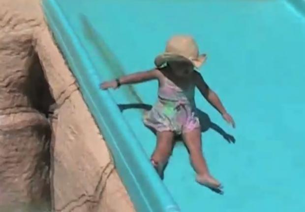 Una niña se hace caca mientras que se desliza por el tobogán a la piscina