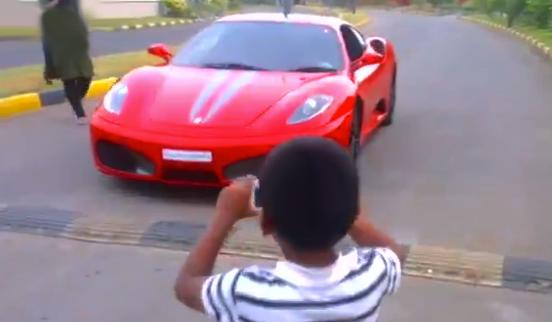 Un niño pequeño conduciendo un Ferrari