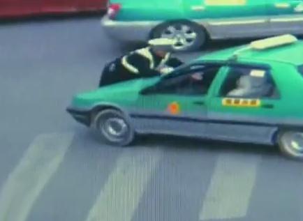 El conductor de un taxi ilegal arranca el coche con un policía encima del capó