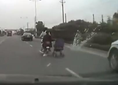 Una mujer china lleva un carrito de bebé de remolque en su moto