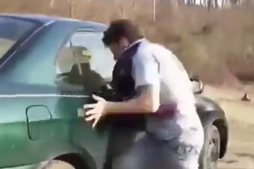 Intentando romper la ventana del coche a cabezazos