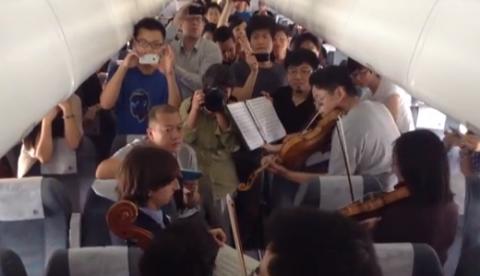 Unos músicos improvisan un concierto en el interior de un avión retrasado