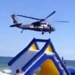 Un helicóptero volando bajo en la playa hace volar un tobogán hinchable con un niño dentro