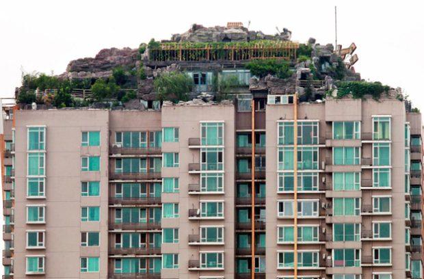 Un hombre chino se construye un monte en lo alto de un bloque de pisos