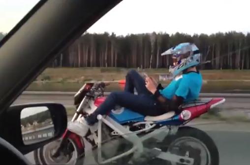 Whatsappeando mientras que va tumbado en la moto