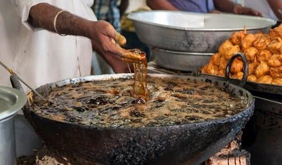 Un cocinero indio mete las manos como si nada en aceite hirviendo