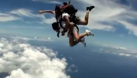 Instructor metiéndole ganchos de derecha a un alumno durante un salto en paracaídas