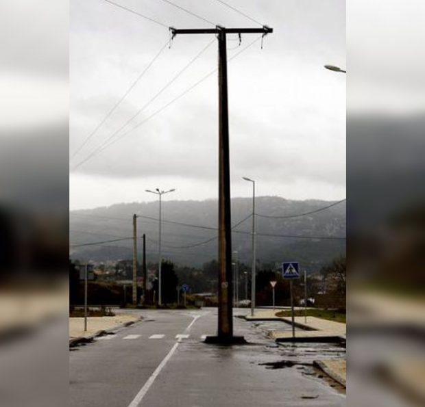 Una carretera abierta al tráfico con un poste de la luz en mitad de uno de los carriles (Galicia)