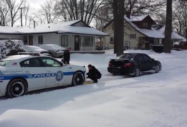 Conductor ayudando a un coche de policía atrapado en la nieve