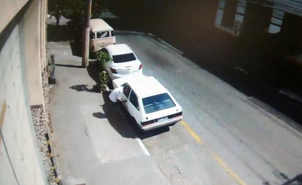 Un hombre derriba con una patada a un ladrón que está intentando robar su coche