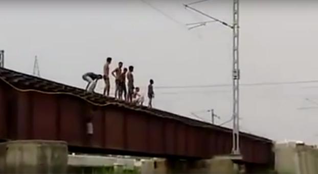 Niños indios saltan desde la vía al río justo cuando llega el tren
