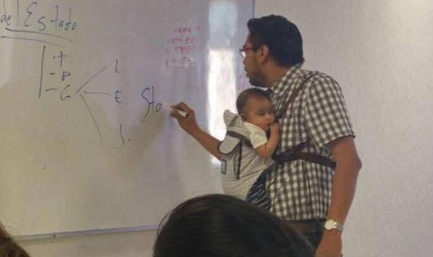 Un profesor universitario da clase con el bebé de una alumna en brazos