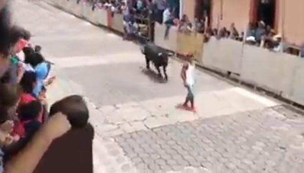 Un grupo de personas intenta recuperar el cuerpo inmóvil de un hombre que fue embestido por un toro