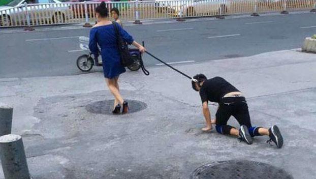 Una mujer pasea a su novio con correa como si fuera un perro