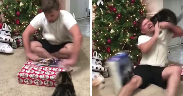 Se pone a abrir su regalo de Navidad todo eufórico y el gato se le tira a la cabeza. Ojo a las heridas...