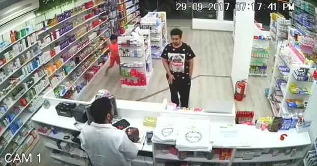 Un niño roba el dinero de la caja registradora de una farmacia