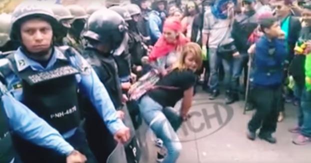 Mujeres haciendo twerking frente a unos policías durante una protesta en Honduras