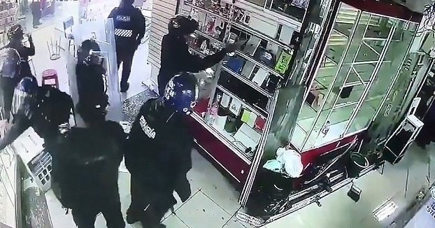La policía antidisturbios grabada saqueando teléfonos en una tienda de un centro comercial