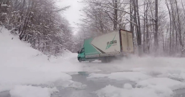 Camionero tomando las curvas derrapando en una carretera de montaña nevada