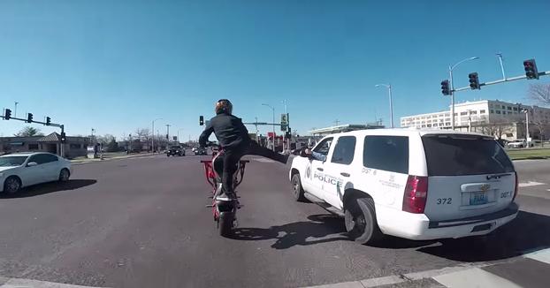 Policía chocándole las cinco a un motorista mientras hace un caballito