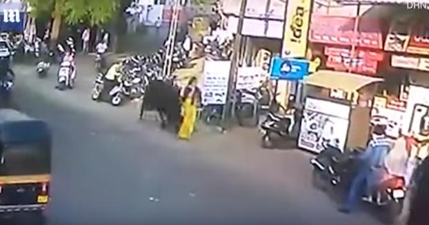 Un toro embiste y lanza por los aires a una mujer en una calle de la India