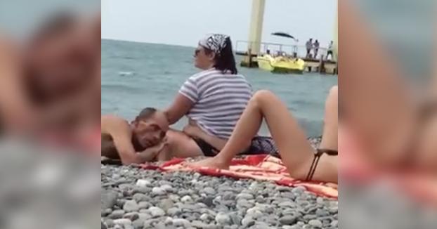 Hombre disfrutando de las vistas en la playa mientras está tumbado al lado de su mujer