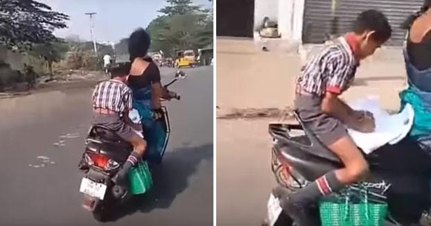 Un niño hace sus deberes sobre una moto en marcha mientras su madre conduce