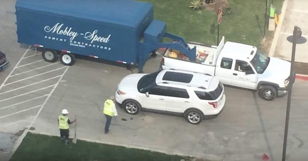 Unos vecinos ven cómo los obreros terminan de poner un parche de hormigón pero se olvidan de señalizarlo