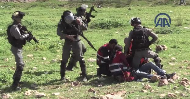 Paramédicos palestinos luchando contra los soldados de ocupación para rescatar a los heridos