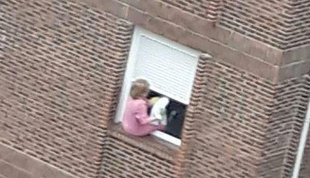 Señora de Santander jugándose la vida limpiando las ventanas de su casa