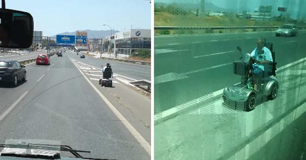 Un hombre circula con una silla de ruedas eléctrica en plena carretera de Málaga