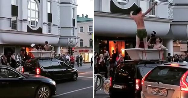 Dos jóvenes se pasean por el centro de Moscú en una bañera montada encima de un coche
