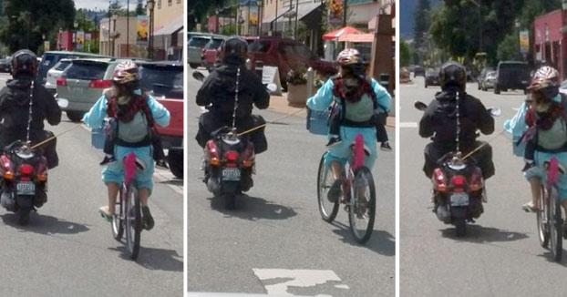 Madre llevando a su hijo en bici en una mochila mientras una scooter tira de ella con una cuerda